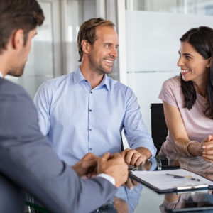 Mature smiling couple meeting financial advisor for investment at office. Financial consultant presents bank investments to man and happy woman. Middle aged couple consulting their bank agent. Saving